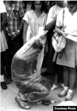 """El artista Juan-Sí González, dentro de un nylon casi hasta la asfixia, hasta que alguien del público lo """"salva"""", performance de Ar-De."""