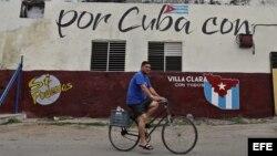 Un hombre cruza en bicicleta frente a un muro con mensajes alusivos a las elecciones generales en Cuba.