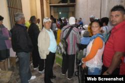 Un grupo de personas esperan en la casa de Lino Tomasen.