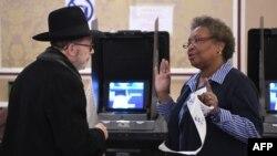 Un votante habla con una trabajadora de un colegio electoral de Nueva York después de depositar su voto en las elecciones de 2016 en EE.UU.