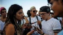 Jóvenes cubanos verifican conexión a internet en sus móviles en La Habana.