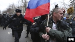 Agentes antidisturbios arrestan a un activista con una bandera nacional rusa