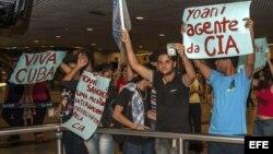 BRA509. RECIFE (BRASIL), 18/02/2013.- Manifestantes que rechazan la visita al país de la disidente cubana Yoani Sánchez, sostienen carteles hoy, lunes 18 de febrero de 2013, en el aeropuerto internacional Guararapes, de la ciudad de Recife (nordeste de Br