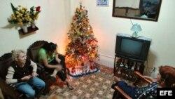 Archivo - Tres mujeres conversan en una casa decorada con un árbol de Navidad.