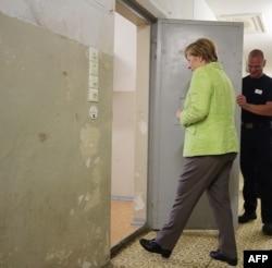 La canciller de Alemania, Angela Merkel, entra el 11 de agosto de 2017 a una celda del Memorial Berlin-Hohenschönhausen en lo que fueran los cuarteles de la STASI en el antiguo Berlín Oriental (Foto: Wolfgang Kumm/AFP).
