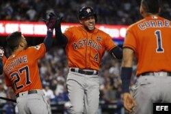 George Springer (c) de los Astros de Houston celebra junto a sus compañeros Jose Altuve (i) y Carlos Correa (d) luego de batear su cuarto jonrón consecutivo de la Serie Mundial 2017 en la segunda entrada del séptimo y definitivo juego