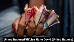 Vendedora de mercado en Manila con dinero en la mano