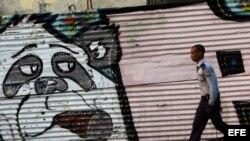 Un policía camina junto a un grafiti en una calle de La Habana (Cuba), hoy, domingo 26 de enero de 2014, dos días antes del inicio de la II Cumbre de la Comunidad de Estados Latinoamericanos y del Caribe (Celac). Calles cerradas, desvíos del transporte pú