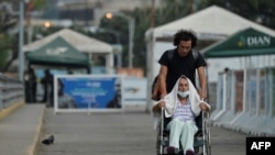 Steve Oliveros conduce a su madre en silla de ruedas de vuelta a Colombia tras serle negado el paso en la frontera para entrar a Venezuela.
