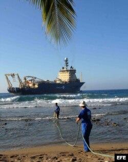 Obreros cubanos arrastran el cable submarino de fibra óptica en la playa de Siboney, en Santiago de Cuba.