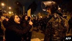 Una mujer iraní que asiste la noche del sábado a una vigilia en memoria de las víctimas del avión ucraniano le habla a un policía que vigila el área (Foto: Mona Hoobehfekr/AFP).