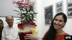 """Yoani Sánchez (d), autora del blog """"Generación Y"""", sonríe con un regalo recibido durante su primera jornada de visita a Brasil en Feira de Santana."""