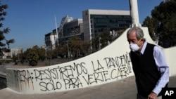 Un hombre que usa una mascarilla pasa junto a un graffiti contra el presidente chileno Sebastián Piñera en medio de la pandemia del coronavirus, en Santiago de Chile. (AP/Esteban Félix)