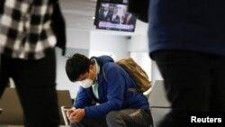 Un viajero en el Aeropuerto Internacional Seattle-Tacoma, en Washington, sigue la intervención del presidente Donald Trump, el viernes 13 de marzo del 2020.