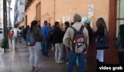 Migrantes hacen fila ante una oficina de Extranjería y Migración en Antofagasta, Chile.