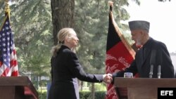 La secretaria de Estado de Estados Unidos, Hillary Clinton a la izquierda, saluda al presidente afgano, Hamid Karzai, a su llegada a una rueda de prensa conjunta en Kabul, Afganistán, el 7 de julio de 2012.