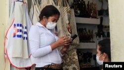 La empleada de una tienda usa una máscara protectora por el coronavirus, en La Habana.
