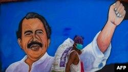 Un indigente pasa protegiéndose ocntra el coronavirus frente a un cartel de mandatario de Nicaragua, Daniel Ortega.