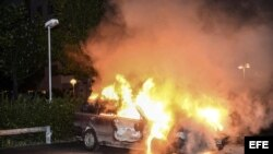 Vista de un vehículo en llamas tras los disturbios registrados en el barrio de Kista, en Estocolmo, Suecia, en la madrugada de hoy miércoles 22 de mayo de 2013.
