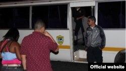 Dos migrantes ilegales son conducidos a un autobús del Servicio Nacional de Migración de Panamá.