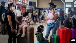 Viajeros con noasobucos esperan sus vuelos en el Aeropuerto Internacional José Martí de La Habana.