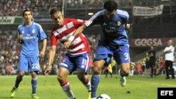 El defensa portugués del Real Madrid Pepe (d) lucha el balón con Dani Benítez, del Granada CF, durante el partido, correspondiente a la segunda jornada de la Liga en Primera División.