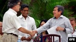 El jefe negociador del gobierno colombiano, Gustavo Bell (i), estrecha la mano del comandante del ELN Israel Ramírez Pineda (d), alias Pablo Beltrán, en La Habana.