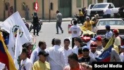 Colectivos apuntando con un arma a la caravana de Juan Guaidó
