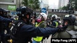 Policías en Hong Kong empujan a periodistas en la manifestación anticomunista del 19 de enero de 2020 (Philip Fong/AFP)