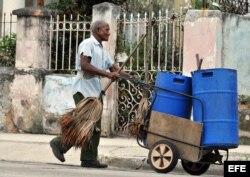 Un anciano barrendero camina por una calle en La Habana.
