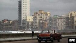 Un viejo auto circula por el malecón de La Habana (Cuba).