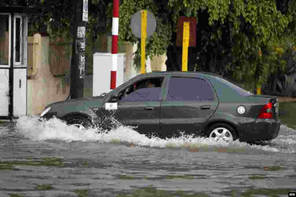 Un vehículo cruza por una calle inundada hoy, miércoles 29 de abril de 2015, en La Habana (Cuba).