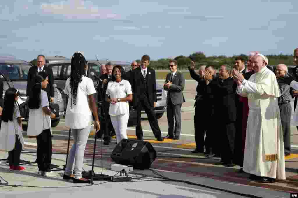 El papa Francisco es recibido por un coro de niños a su llegada al aeropuerto de Santiago de Cuba.