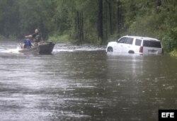 Rescatistas acuden en auxilio de personas atrapadas en auto en una calle inundada de Latta, Carolina del Sur.