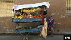 Un hombre vende frutas y verduras en una carretilla (diciembre, 2014).