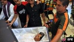 HAB100. LA HABANA (CUBA), 23/07/2012.- Reinaldo Payá (c), hijo del fallecido opositor Oswaldo Payá, observa los restos de su padre hoy, lunes 23 de julio de 2012, en una iglesia de La Habana (Cuba). Unas 400 personas recibieron hoy los restos mortales de