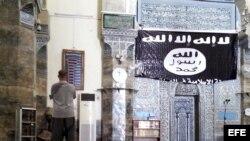 Un hombre reza en la mezquita de Al-Noori Al-Kabeer, junto a una bandera del grupo yihadista Estado Islámico (EI) en Mosul, Irak.