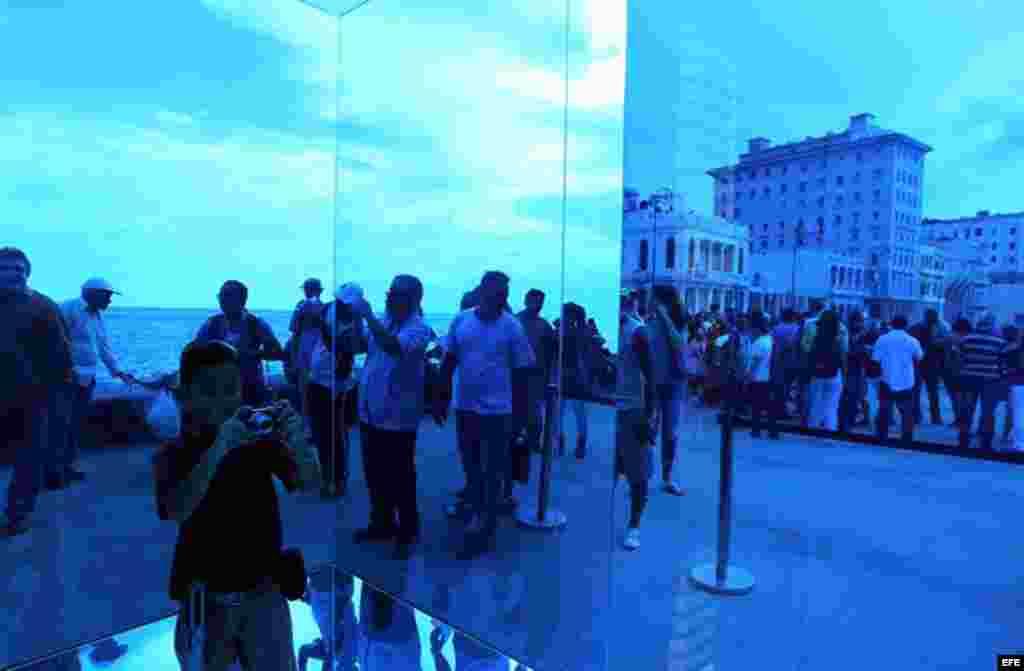 """Un niño toma fotos dentro de la obra """"Cubo Azul"""" de la artista Rachel Valdés expuesta en el Malecón hoy, domingo 24 de mayo, donde ha sido inaugurada la exposición """"Detrás del Muro"""" como parte de la XII Bienal de Arte de La Habana."""