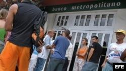 Varias personas hacen colas en un Banco de La Habana.