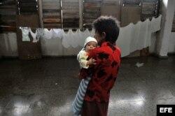 Una mujer carga un bebé en un albergue en el municipio de La Coloma, provincia de Pinar del Río.