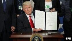 El presidente estadounidense, Donald J. Trump (c), enseña la firma de la orden ejecutiva para destinar fondos federales a la construcción del muro con México durante una ceremonia en el Departamento de Seguridad Nacional en Washington, Estados Unidos, ho