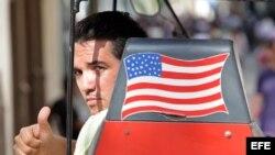 Un hombre saluda desde una bicitaxi con la bandera de EEUU. (Archivo)