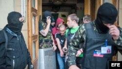 Fuerzas prorrusas enmascaradas resguardando el ingreso a una estación de TV regional en Donetsk