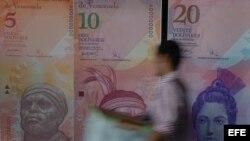 Un hombre pasa frente a varios modelos de billetes venezolanos.