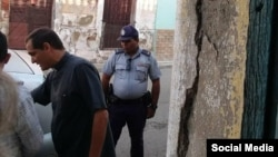 El sacerdote católico Castor Álvarez interpela a la policía ante la detención del periodista independiente Henry Constantín. (Facebook).