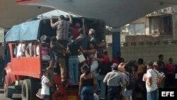 Varias personas intentan subir a un camión que funciona como transporte público