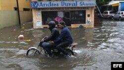 Un motociclista avanza por una calle inundada el miércoles 10 de junio de 2013, en Santo Domingo (República Dominicana).