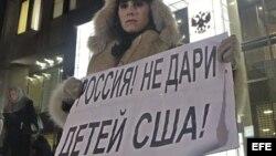 Una mujer protesta en contra de la prohibición de adopción de huérfanos rusos a ciudadanos americanos a las puertas del Consejo de la Federación en Moscú (Rusia).