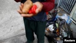 Un hombre sostiene las verduras que encontró en un contenedor de basura en Caracas, Venezuela, el 27 de febrero de 2019.