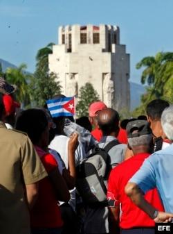 Varias personas esperan cerca de la entrada del cementerio Santa Ifigenia.